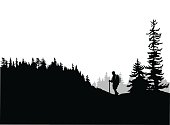 A vector silhouette illustration of a young man hiking through the deep forest up a hill.