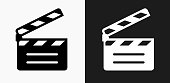 Movie Clapper Icon on Black and White Vector Backgrounds. This vector illustration includes two variations of the icon one in black on a light background on the left and another version in white on a dark background positioned on the right. The vector icon is simple yet elegant and can be used in a variety of ways including website or mobile application icon. This royalty free image is 100% vector based and all design elements can be scaled to any size.