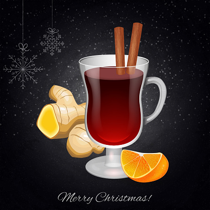 Mulled wine in the wineglass with cinnamon sticks and orange on blackboard background