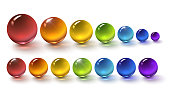 Set of multi-colored glass balls on a white background, round drops of rainbow colors