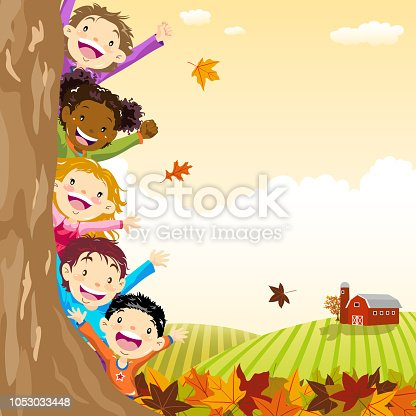 istock Multi-Ethnic Kids Hiding Behind Autumn Tree 1053033448