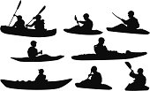 Multiple silhouettes of people canoeing