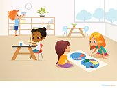 Multiracial children in Montessori classroom. Girls viewing world map and painting picture and boy taking container off shelf. Educational activities concept. Vector illustration for poster, website.
