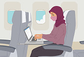 Muslim business woman working on laptop inside airplane wearing face mask during sars-cov-2 pandemic