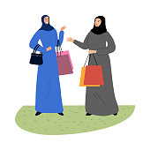 Muslim girls in a traditional ethnic hijab standing with colourful shopping bags. Beautiful girls shopping concept. Isolated vector icon illustration on white background in cartoon style.