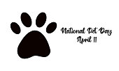 istock National Pet Day on April 11 - text calligraphic lettering. Dog or cat pet paw flat icon silhouette. Isolated vector illustration on white background. Black and white print, greeting card or web banner 1302792096