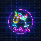 Neon cocktails bar sign in circle frame with lettering on dark brick wall background. Glowing gas advertising