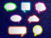 Neon colorful speech bubbles on brick wall background.