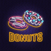 Neon donuts retro sign on brick wall background. Design for cafe, restaurant. Vector illustration. Neon design for pub or fast food business. Light sign banner. Glass tube.