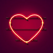 Neon heart signboard on the red background.