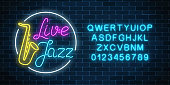 Neon jazz cafe with live music and saxophone glowing sign with alphabet on a dark brick wall background. Glowing street signboard of bar with karaoke and blues singers. Vector illustration.