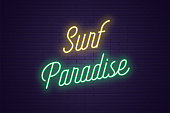 Neon lettering of Surf Paradise. Glowing headline, bright neon cursive text of Surf Paradise. Title template for web banner and poster. Yellow and green color