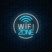 Neon sign of free wifi zone in circle frame on dark brick wall background. Wireless connection free access in cafe