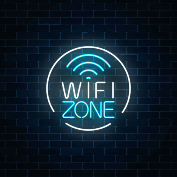 neon sign of free wifi zone in circle frame on dark brick wall background. wireless connection free access in cafe - wireless technology stock illustrations, clip art, cartoons, & icons