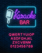 Neon signboard of karaoke music bar with alphabet. Glowing street sign of a nightclub with live music.