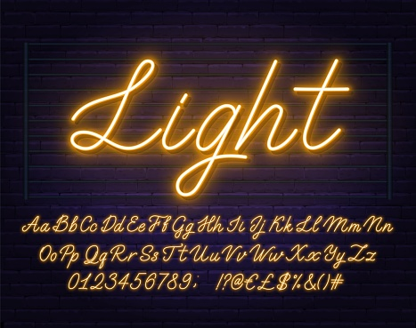 Neon yellow script font. Glowing alphabet with letters, numbers and special characters on a brick background.