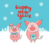 """New Year card. Two cartoon pigs against the background of snow-covered houses and the inscription """"Happy New Year"""""""