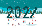 New year christmas landscape. 2021 lettering is decorated with garlands. Winter scene in park. People are having fun, ice skating, walking with their family, making snowman. Holiday eve