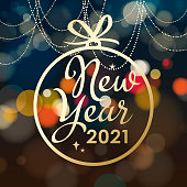 Join the celebration party for the New Year 2021 with gold colored decorations bauble on the colorful lights background