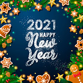 Celebrate New Year 2021 with sugar Powder lettering on the wreath background containing gingerbread cookies, acorns, gold stars, pine tree leaves, berry fruits and spot lit