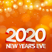 Join the celebration party for 2020 New Year's Eve with folded paper craft and gold colored ribbons on orange colored lights background