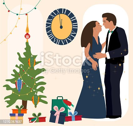 istock New Year`s night.Man and woman celebrating, kissing to the chimes.Christmas tree with toys and garlands,fireworks. 1270287637