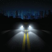 Night Road with the Car and the City on the Horizon