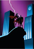 A vector illustration of two superhero silhouettes in big city setting. Wide space available for your copy. AICS5 file included.
