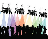 Large crowd of people dancing with colored concert lights above them