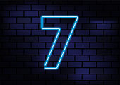 Number 7 Sign Blue Neon Light On Dark Brick Wall. Horizontal composition with copy space.