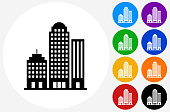 Office Buildings.The icon is black and is placed on a round blue vector button. The button is flat white color and the background is light. The composition is simple and elegant. The vector icon is the most prominent part if this illustration. There are eight alternate button variations on the right side of the image. The alternate colors are orange, red, purple, yellow, black, green, blue and indigo.