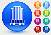 Office Skyscrapers Icon on Shiny Color Circle Buttons. The icon is positioned on a large blue round button. The button is shiny and has a slight glow and shadow. There are 8 alternate color smaller buttons on the right side of the image. These buttons feature the same vector icon as the large button. The colors include orange, red, purple, maroon, green, and indigo variations.