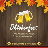 Oktoberfest invitation with beer and autumn leaves on wood background