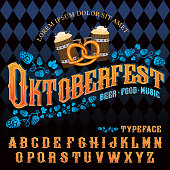 Vector hand crafted font in vintage style with hops, beer mugs, pretzel and traditional Oktoberfest rhombus pattern on background.
