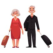 Old couple of man and woman with suitcases in airport