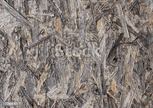 istock Old OSB board damaged by water and sun - abstract messy dirty textured wooden wall background with amazing unique natural details with visible discoloration and deposits in shades of beige and brown 1226905171