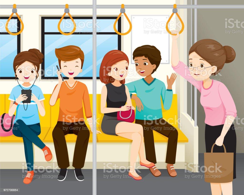 歳の女性が電車内に立っています若い人たちが誰も彼女のために立って座っ