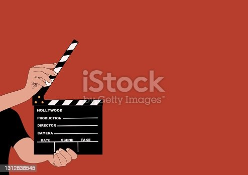 istock Open film clapper held by the hands of a young man. 1312838545