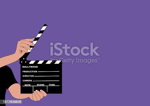 istock Open film clapper held by the hands of a young man. 1312838839