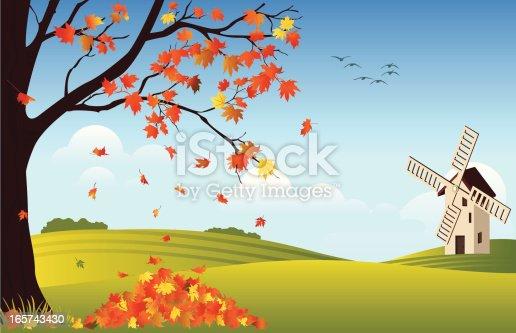 istock Orange leaves falling off tree in fall with windmill in rear 165743430