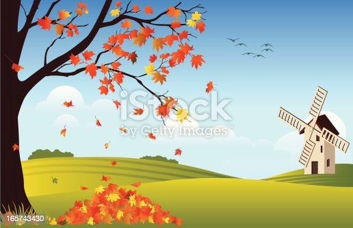 istock Orange leaves falling off tree in fall with windmill in rear 165743430