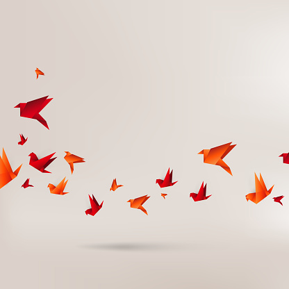 Origami red birds on brown background