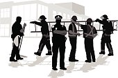 A vector silhouette illustration of working professionals including a janitor, firemen, police officer, and construction crew members.