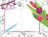 Overhead Desk Mockup With Tulips, Notepad And Scissors on a marble base.