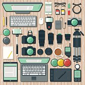 An overhead view of items you might find on the desk of a photographer, including: Laptop, tablet, smart phone, computer, lenses, DSLR cameras, sync cables, tripods, lens filters, light meters, memory cards, remote triggers and so on. File is organized into layers and each icon is properly grouped for easy editing.