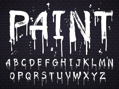 Paint dripping paint font for latin alphabet isolated on dark background with bricks. White oil letters