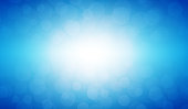 Soft pastel blue colour shining star horizontal background stock photo. Looks like twinkling lights light shiny background. Vignette, vignetting, copy space. No people. No text. Apt for party, Xmas, Christmas, New Year's eve, birthday party celebration backdrop, wallpaper,  romantic gift wrapping paper. A bright white light brightens up the centre, middle or center of the frame. Dark blue corners.