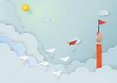Paper airplanes flying on blue sky to the target of red flag on hand of businessman.Paper art style of start up and business teamwork creative concept idea.Vector illustration