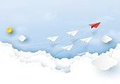 Paper airplanes flying on clouds and blue sky.Paper art style of business teamwork creative concept idea.