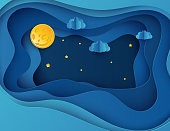 Paper art moon, fluffy clouds and stars in midnight.